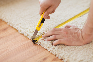 Installer cutting carpet
